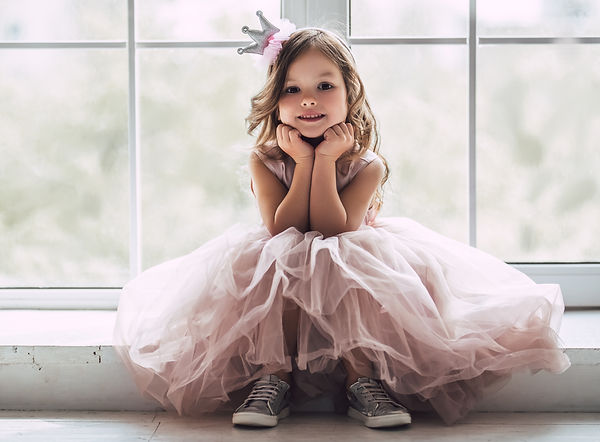 Little cute girl in beautiful dress is s