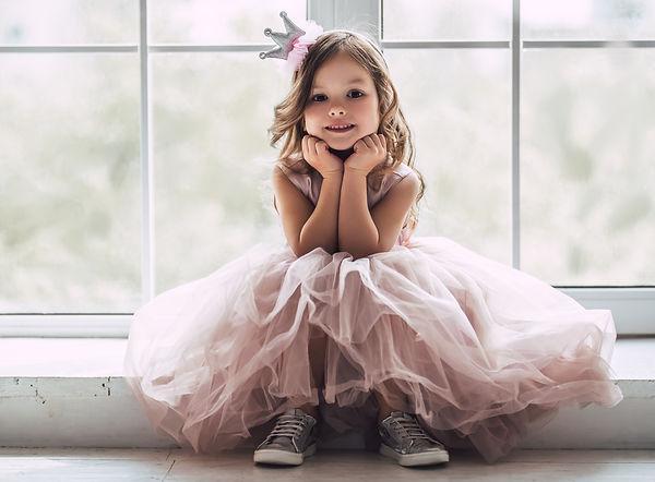 Little cute girl in beautiful dress is s