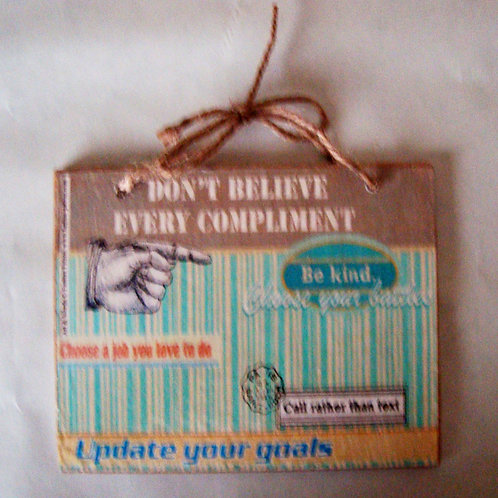 """Don't believe every compliment"", wooden sign"