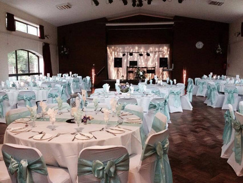 White stretch covers and tiffany taffeta sashes along with hurricane lamp centrepieces