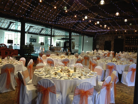 White stretch covers and orange organza sashes