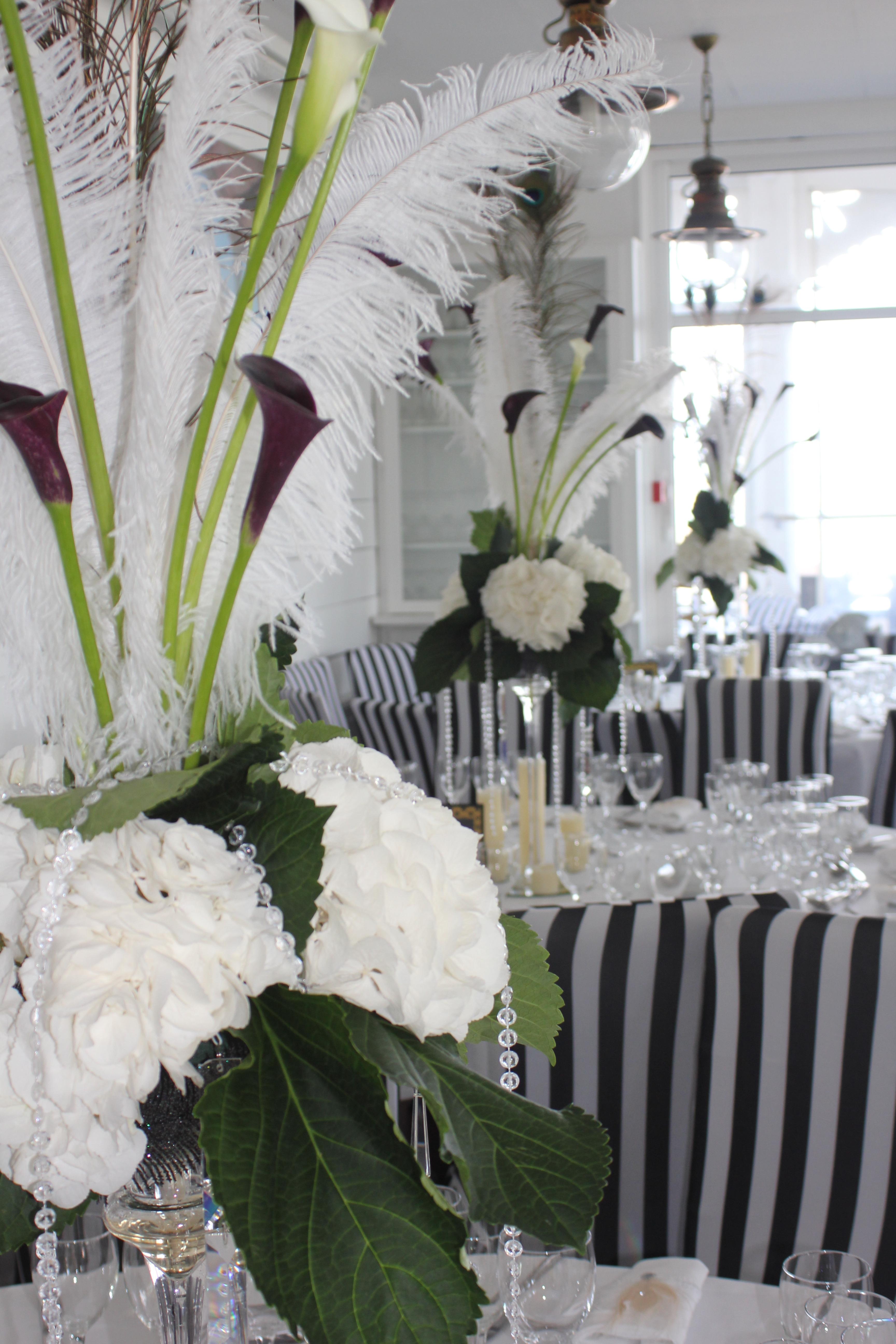Centre de table haut avec hortensias, callas, plumes d'autruche et plumes de paon