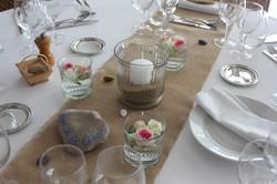 Centre de table avec fleurs flottantes et bougie posée sur le sable