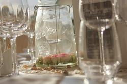 Roses mini eden flottantes dans un photophore avec une bougie suspendue