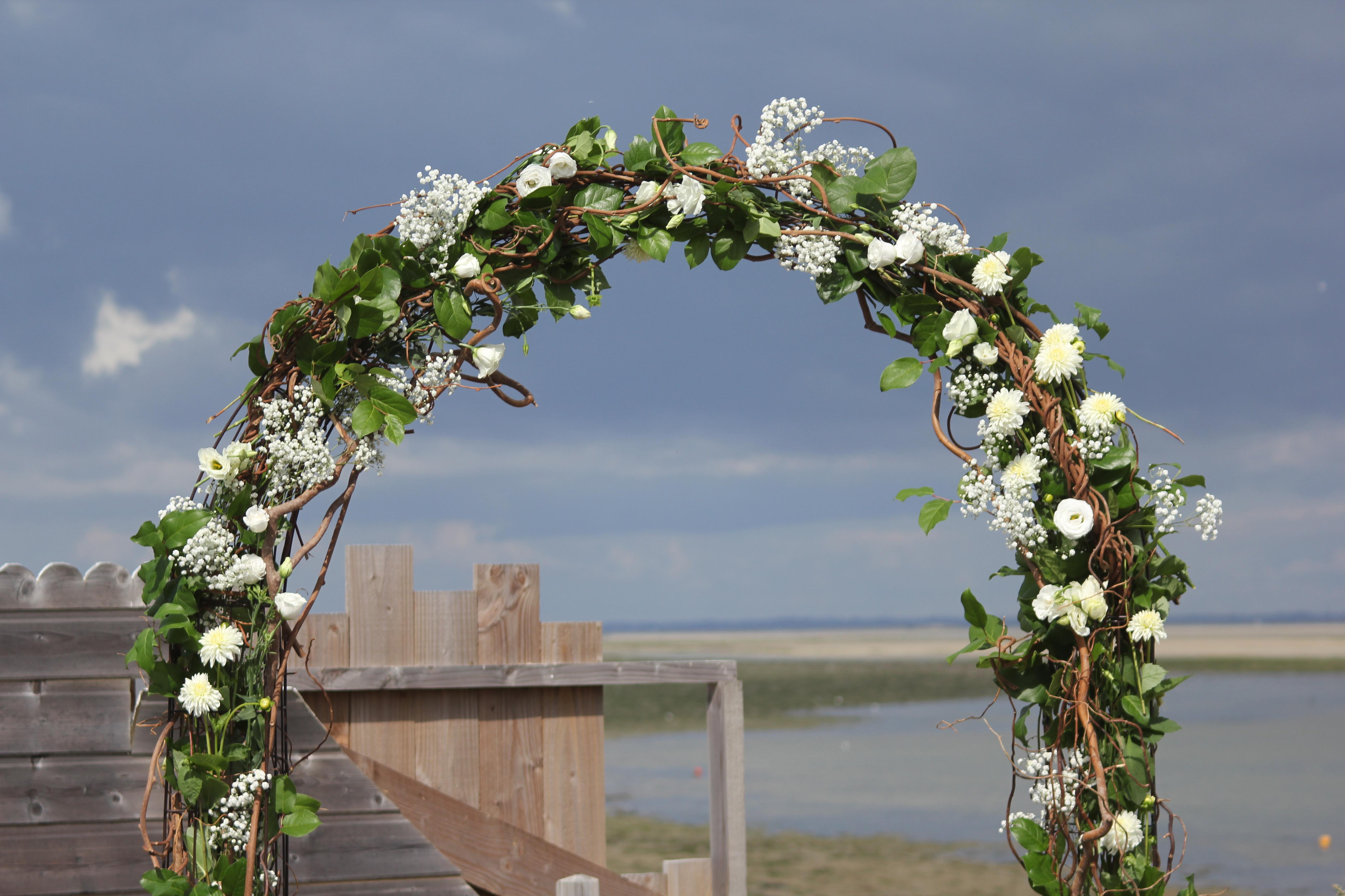Arche cérémonie laïque avec branches tortueuses, feuillage et fleurs blanches