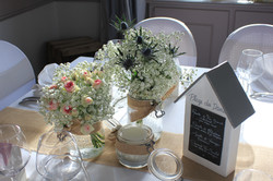 Centre de table gypsophile, roses mini eden et chardons dans bocaux sur toile de jute