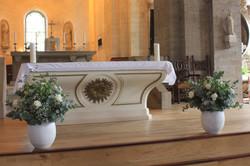 Décoration de l'autel : composition de roses blanches et d'alstromeria avec de l'eucalyptus