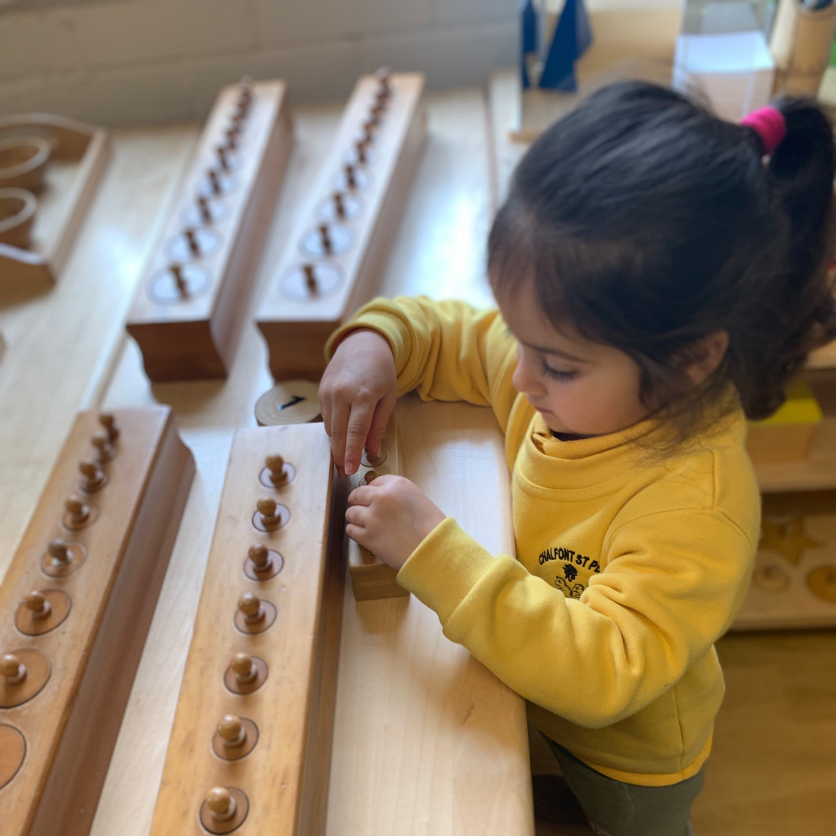 Knobbed cylinders, usinging fine motor skills to prepare the hand for writing practice as well as using visual perception to recognise size and dimension.