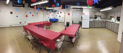 This image shows the birthday party room with three large tables with tabl clothes ad decorations on the table and around the room.