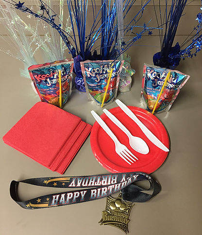 This image shows the items provided for the party which include plates, napkins, juice drinks and some decorations. There is also a birthdy party medal that is awarded to the birthday boy or girl.