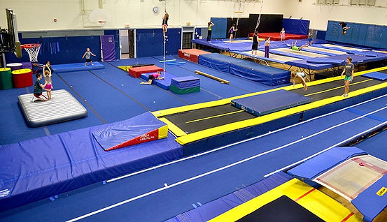 This image shows the gym from a high angle wth childre on the trampoline, the tumbling trampoline and the student being spotted in a back handspring.