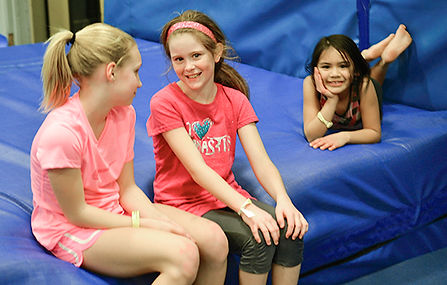 Children are relaxing at the gym and visiting with each other.
