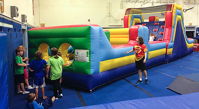 Children are playing on a large inflatable obstacle course.