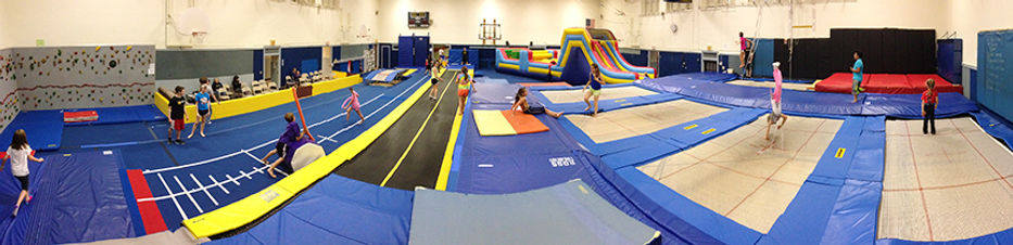 Children are playing at the gym during Super Saturday Open gym at the Emporia location. You can see the trampolines, the inflatable obstacle course, the tumble trampoline and the parents waitng area.
