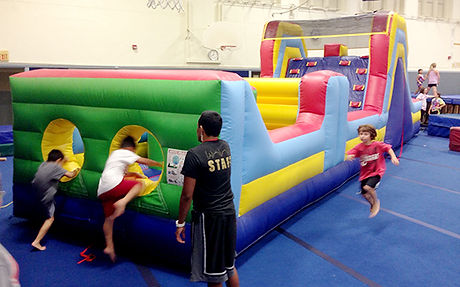 Children are paying on a large inflatable obstacle course.