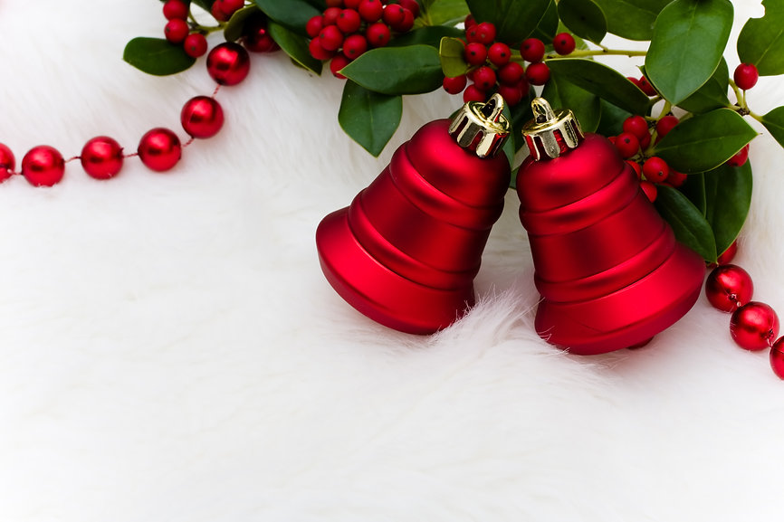 Red bells and holly and berries on a whi