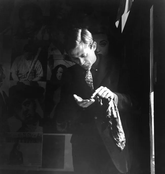 A man in soft afternoon light counts his change in a street photo made by Imogen Cunningham.