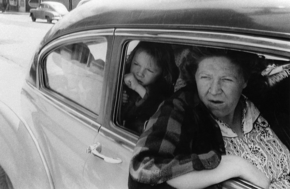 One of the 83 images in Robert Frank's defining work The Americans. A whole family piles into a 50s style car as they head into town. Black and white image of a mother and daughter looking out the car window.