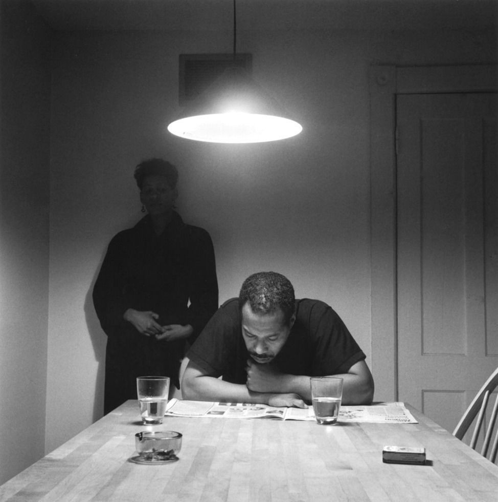 A woman stands behind a man as he reads a newspaper at the kitchen table. A piece from Carrie Mae Weems' 1990 project The Kitchen Table Series