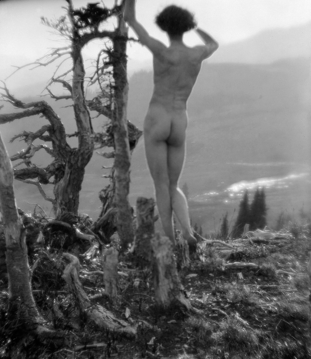 Roi Partridge, Immogen Cunningham's husband, poses nude atop Mt. Rainier in Washington state. He is facing away from the camera posing next a tree while looking out on the mountain range. Black and white photograph.