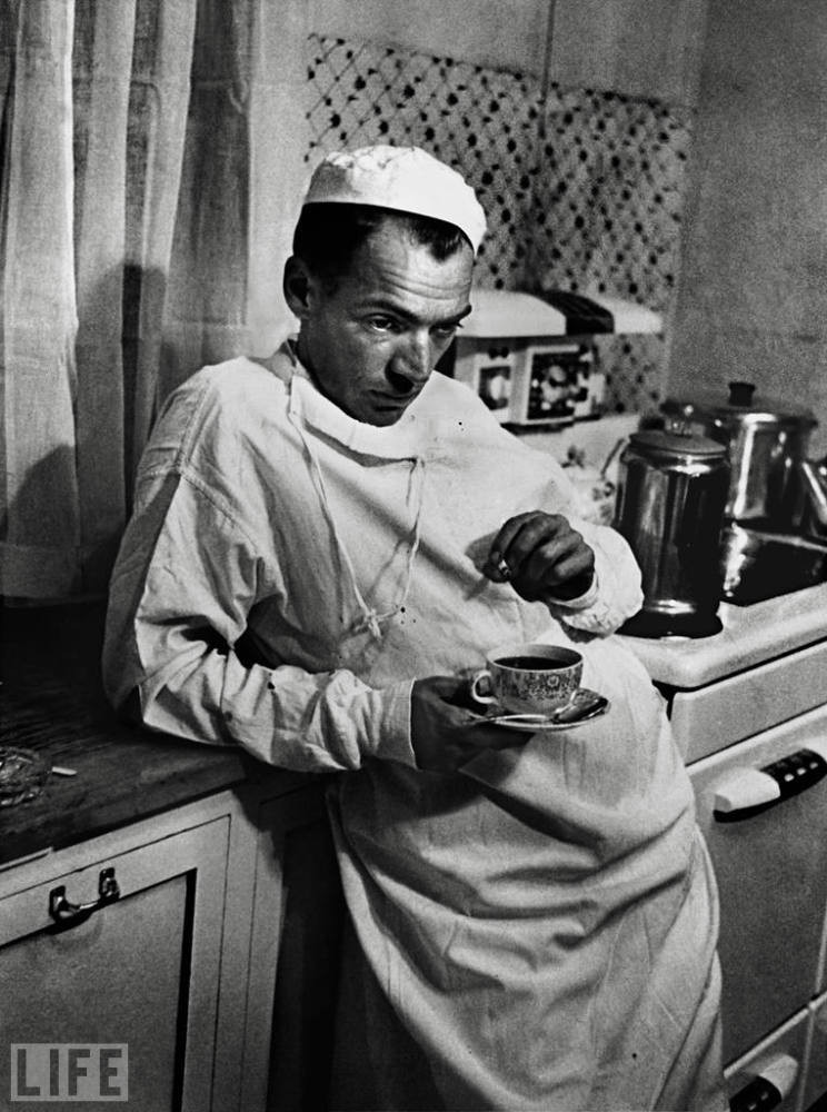 The black and white image made by Eugene Smith for LIFE magazine and the photo essay Country Doctor. Dr. Ceriana leans against the counter as he steeps a cup of tea, deompressing after a long and difficult surgery.