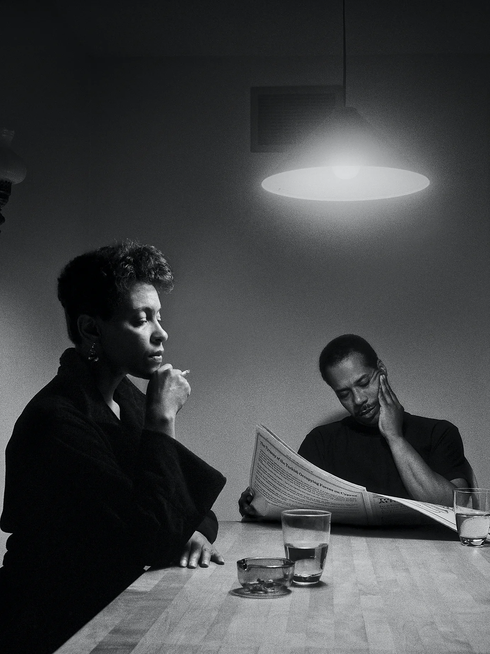 A woman sits, straight backed, at a table with a cigarette under her chin. The man at the end of the table is reading a newspaper while rubbing his face. A piece from Carrie Mae Weems' 1990 series The Kitchen Table Series.