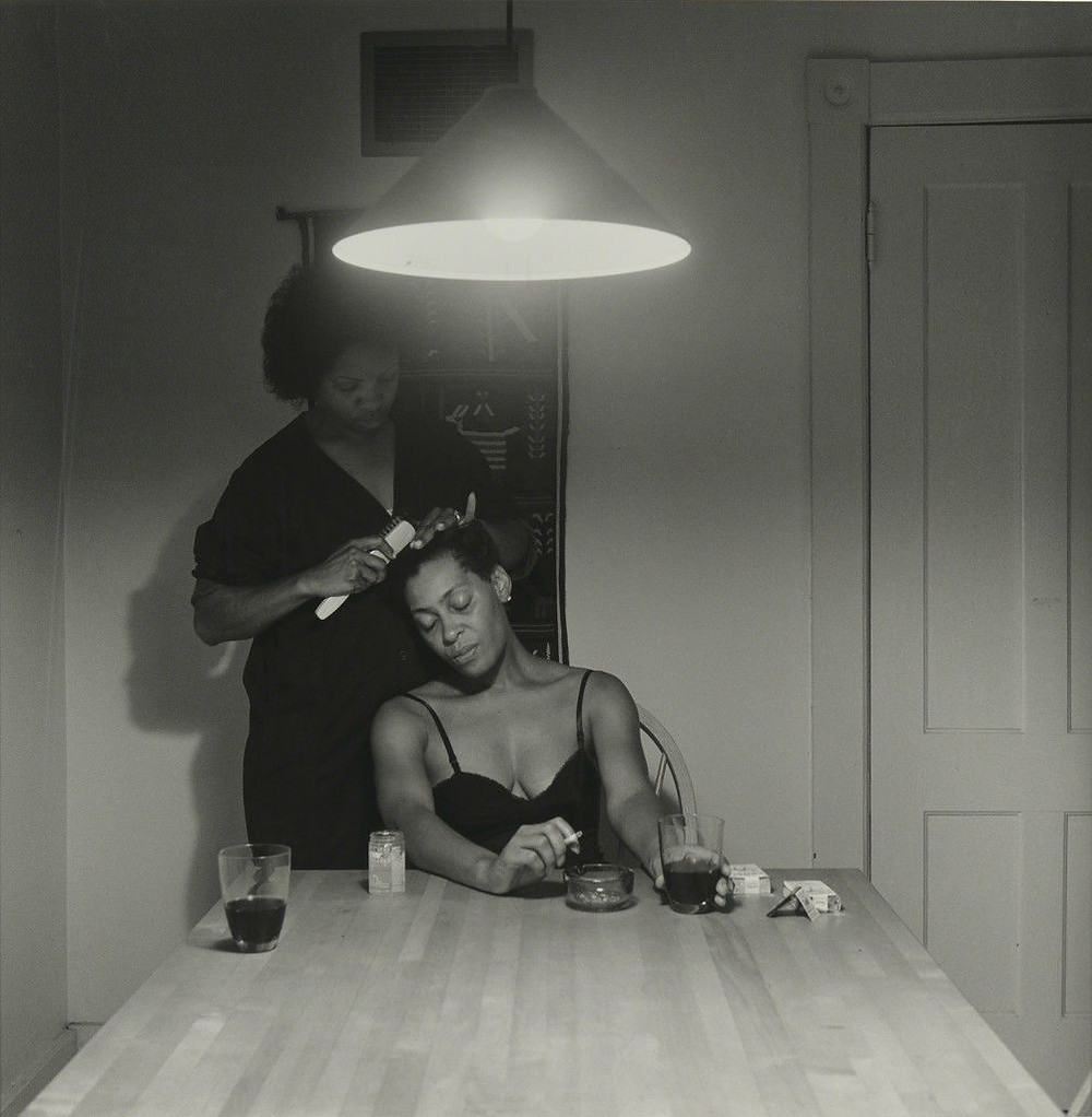 A monther and daughter sit at the end of a table. The mother is combing her adult daughter's hair while the daughter ashes a cigarette. This black and white photo is from Carrie Mae Weem's 1990 piece The Kitchen Table Series.