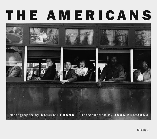 A broadside view of a New Orleans trolley filled with a diverse group of people. Each window perfectly frames a different person and they perfectly describe how diverse American culture is. It is a black and white image with a white man, white woman, two white children, a black man and a white woman as the subjects.