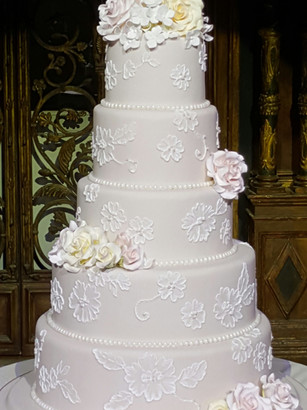Five tier wedding cake with clusters of sugar flowers and intricate lace design