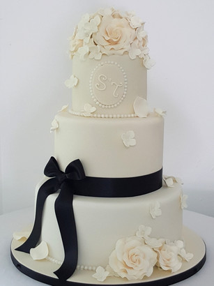 Monochrome white and black three tier wedding cake with sugar roses and petals