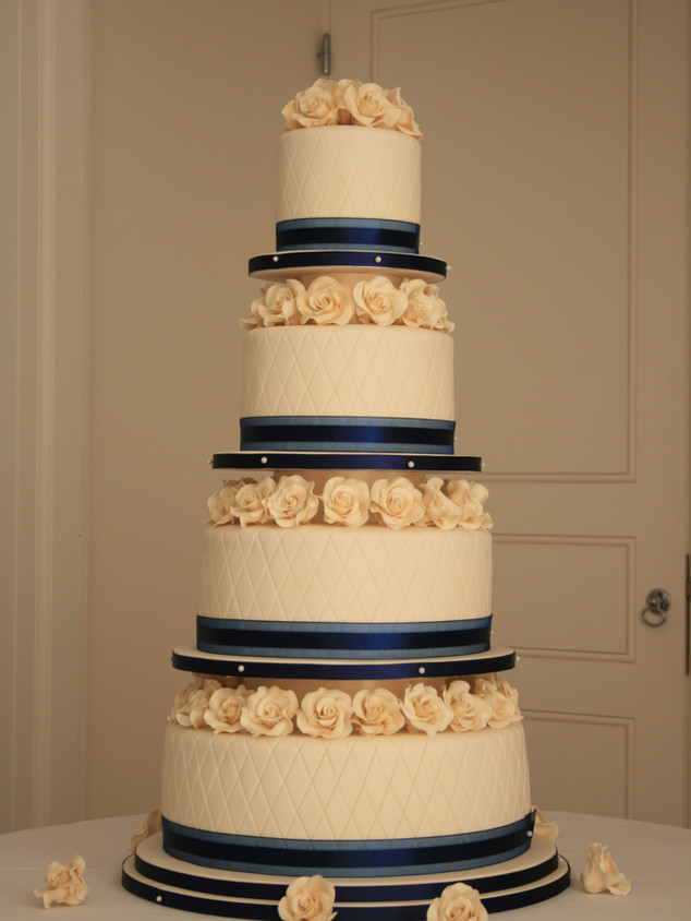Creme and Blue wedding cake with creme colour sugar roses and cake topper.