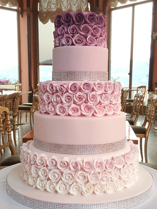 Five tier wedding cake with rows of beautiful shades of pink roses