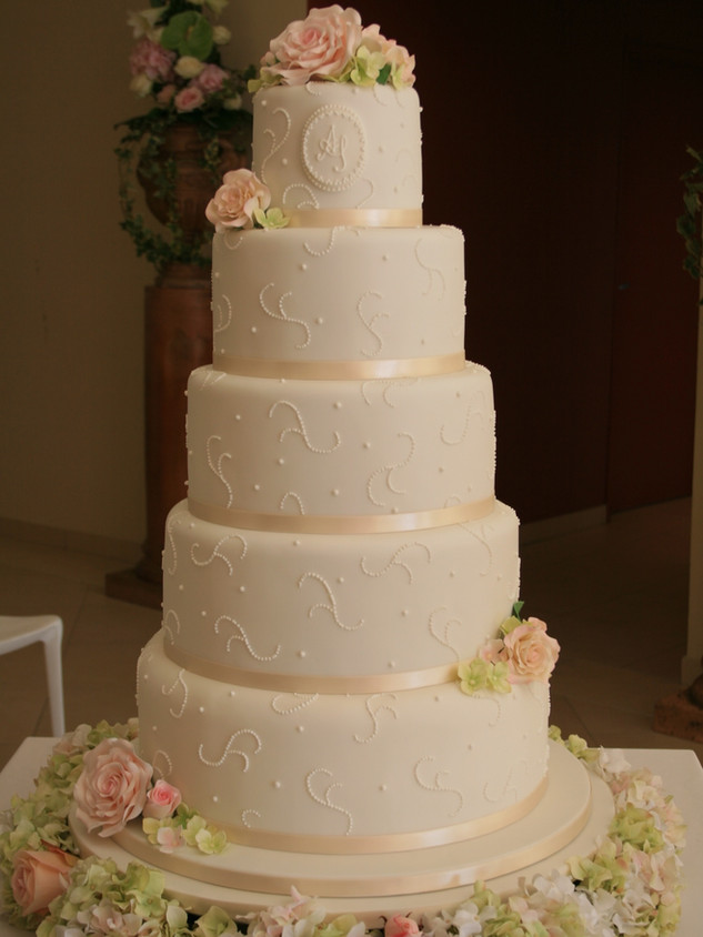 Five tier ivory wedding cake with personalised monogram and clusters of roses and hydrangeas