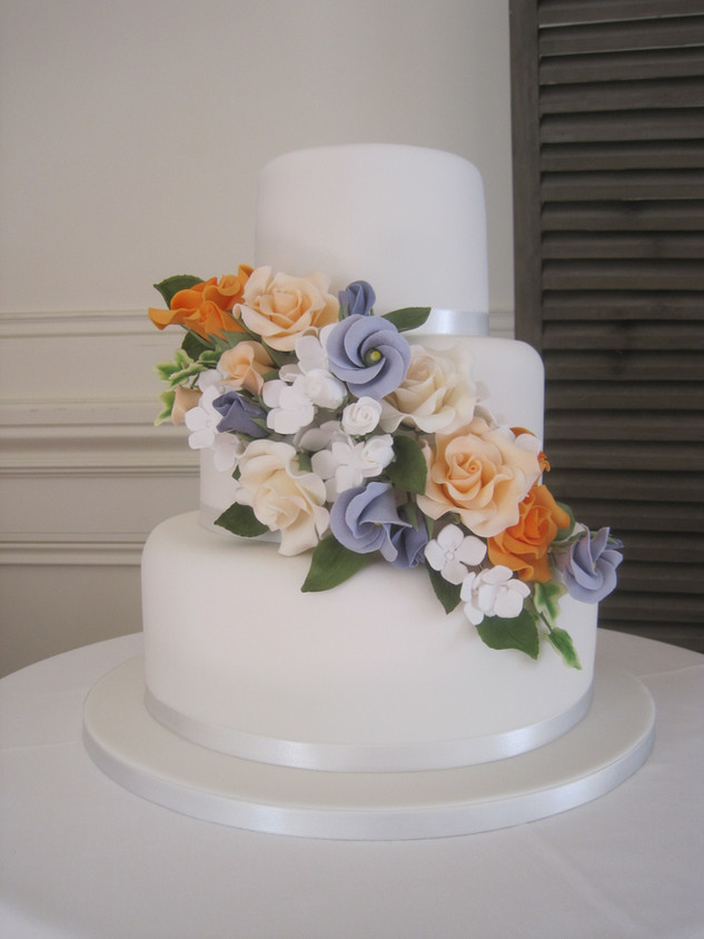 Colourful cluster of sugar flowers on a three tier white wedding cake
