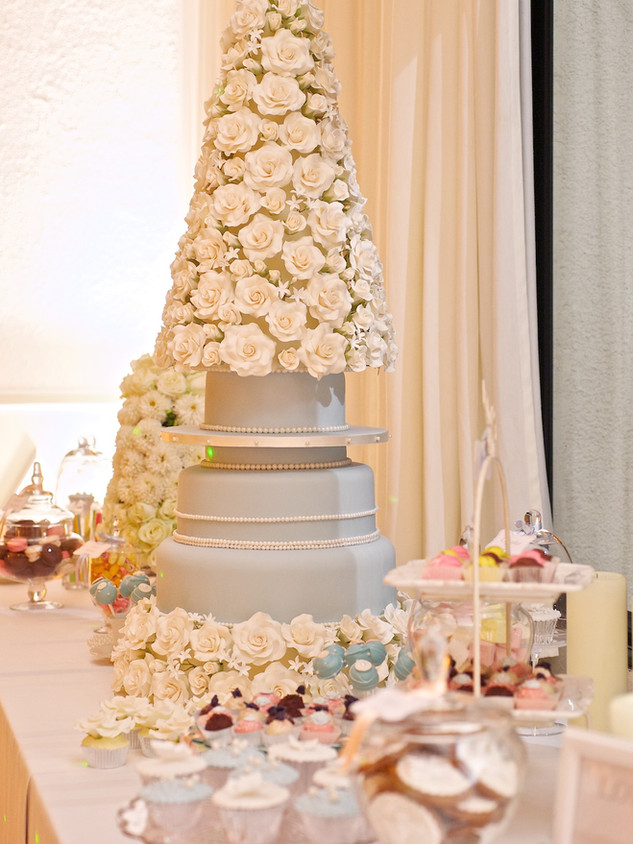 Pyramid wedding cake tower filled with sugar roses, stephanotis and small white flowers.