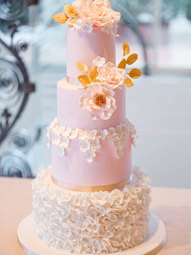 Pink, white and gold wedding cake with sugar peonies, ruffles and gold leaves