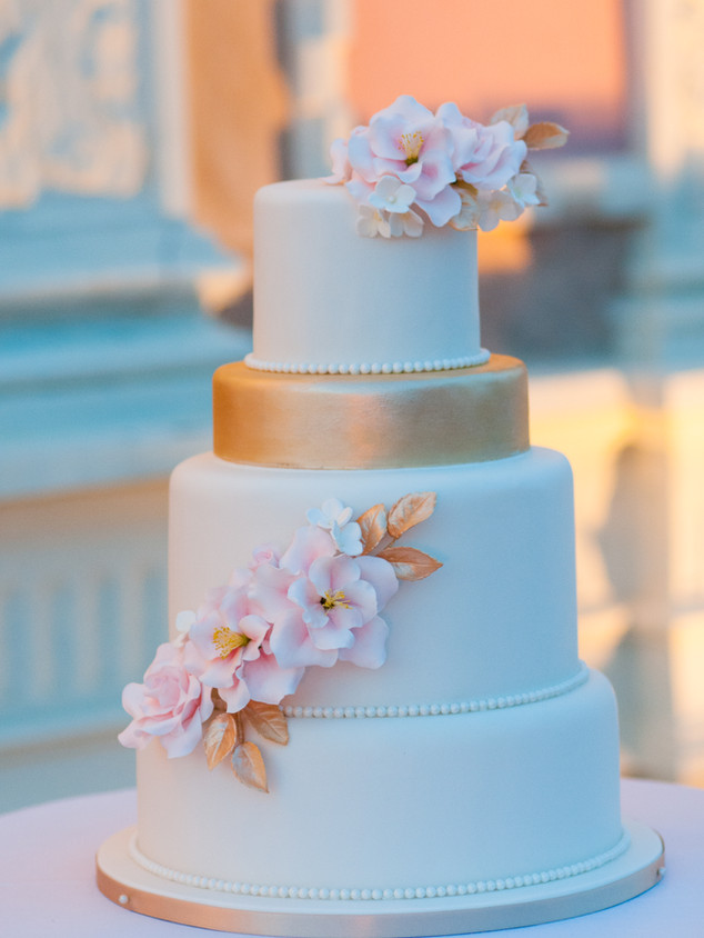 White, and gold wedding cake with delicate pink sugar flowers and gold dusted leaves