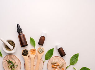 Various herbs, essential oils and supplements with wooden spoons and discs