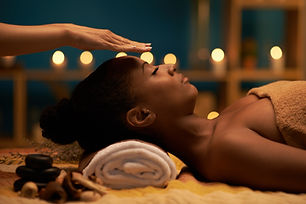 BIPOC person receiving a reiki treatment with candles in the background