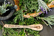 Kitchen-Witch wooden spoon next to a basket of fresh rosemary and lavendar