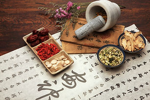 Containers and mortar and pestle with various chinese herbs on top of a parchment with Chinese characters