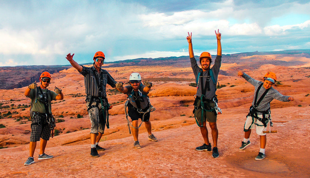 People standing on rocks in moab utah wearing harnesses and helmets at the zip line.