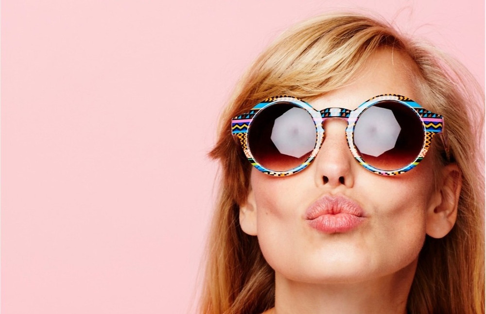 Blonde haired woman wearing multi-colored sunglasses blowing a kiss