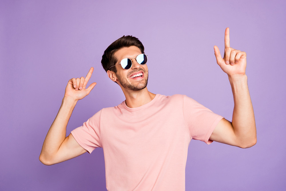 white male wearing a pink shirt and sunglasses smiling with finger guns pointed in the air.