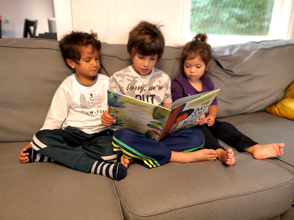 Three young children sitting on a couch with the middle child reading The Day You Begin to the other two.