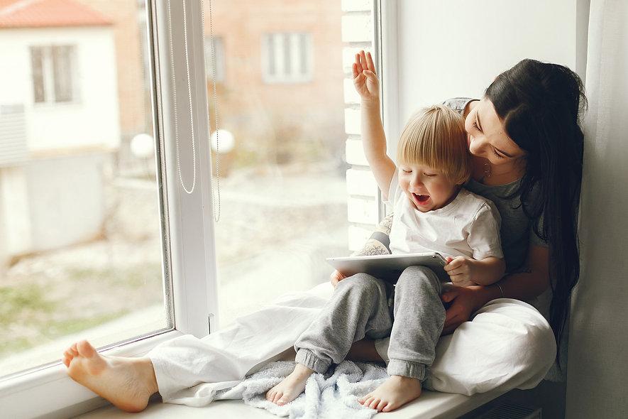Mae com filho ao lado das janelas PVC