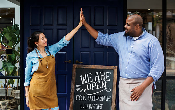 Man and woman in front of open business