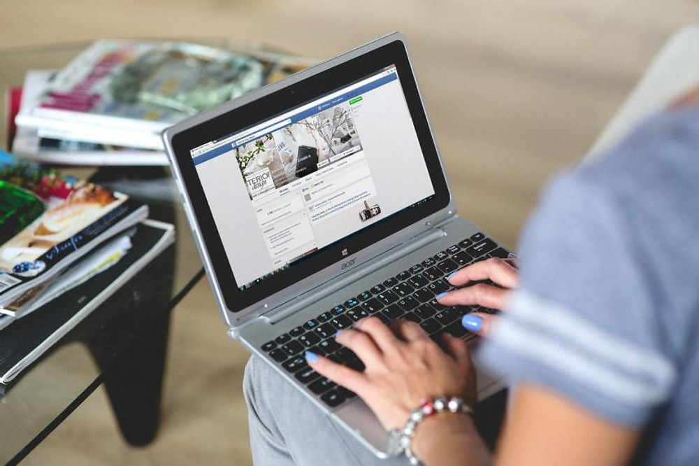 a woman using facebook on a computer