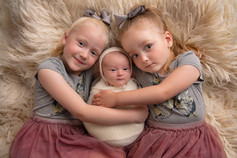 Photograph of a newborn baby girl and her sisters by Christchurch newborn baby & family photographer Kirsten Naomi Photography