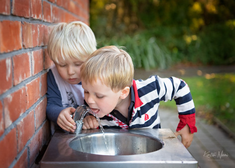 Portrait of two boys playing with a water fountain by Christchurch family photographer Kirsten Naomi Photography    Family Portraits   Lifestyle Photography   Environmental Portraits   Simply Authentic